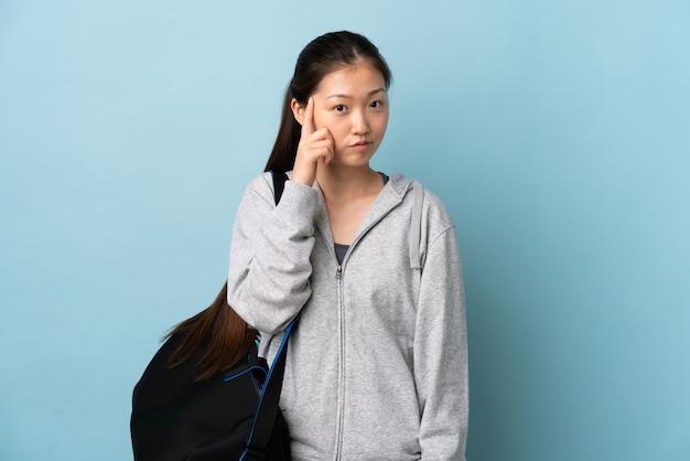 Jonge sport chinese vrouw met sporttas over geïsoleerd blauw die een idee denken