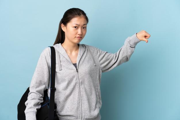 Jonge sport chinese vrouw met sporttas over geïsoleerd blauw met duim neer met negatieve uitdrukking