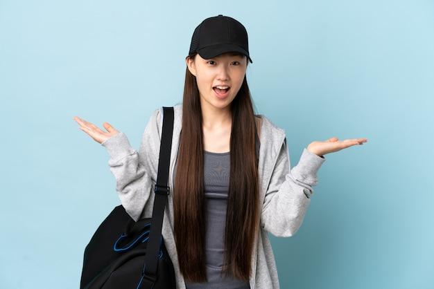 Jonge sport chinese vrouw met sporttas over geïsoleerd blauw met geschokte gelaatsuitdrukking