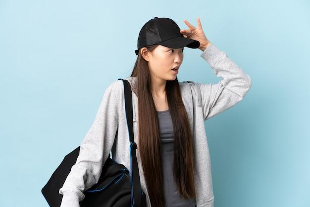Jonge sport chinese vrouw met sporttas over geïsoleerd blauw met verrassingsuitdrukking terwijl op zoek kant