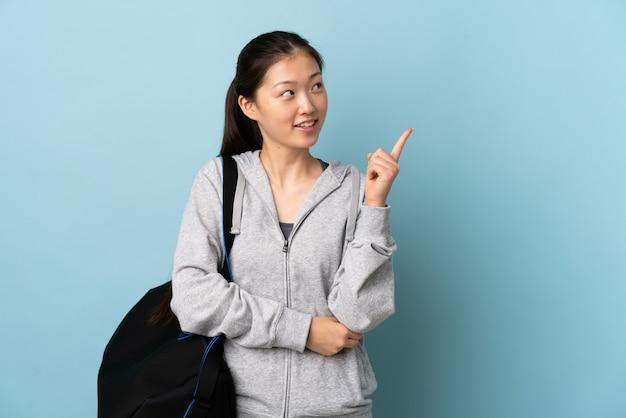 Jonge sport chinese vrouw met sporttas over geïsoleerde blauwe muur die een groot idee benadrukken
