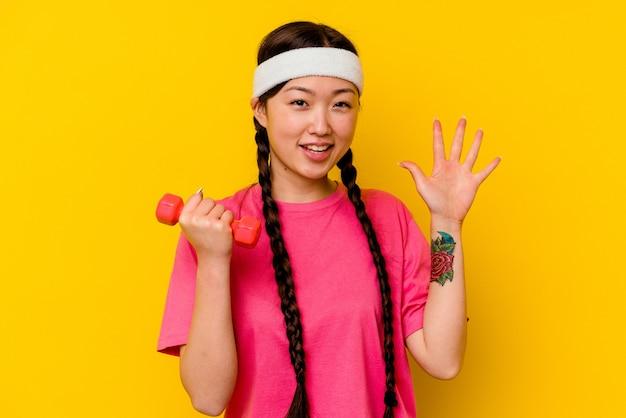 Jonge sport chinese vrouw vrolijk lachend tonend nummer vijf met vingers.