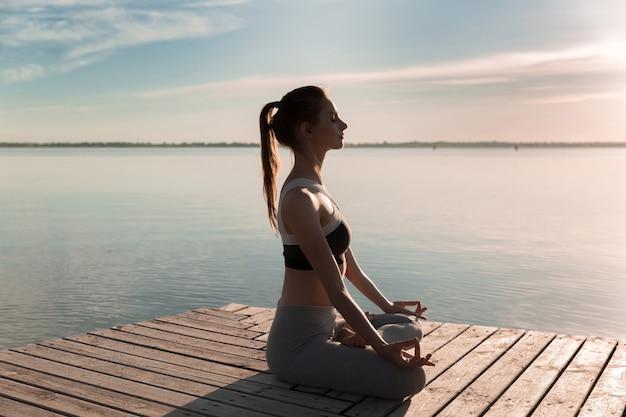 Jonge sport dame op het strand maken meditatie-oefeningen.