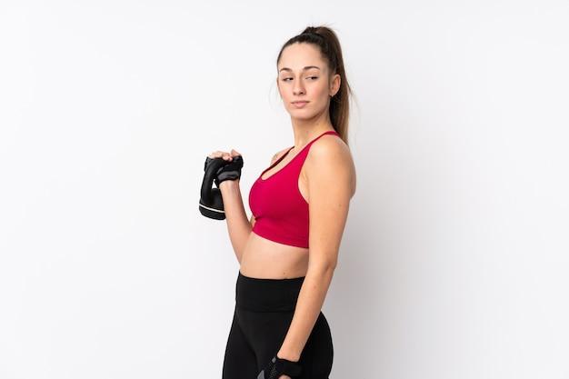 Jonge sport donkerbruine vrouw over geïsoleerde witte muur die gewichtheffen met kettlebell maken