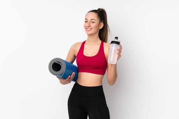 Jonge sport donkerbruine vrouw over geïsoleerde witte muur met de fles van het sportenwater en met een mat