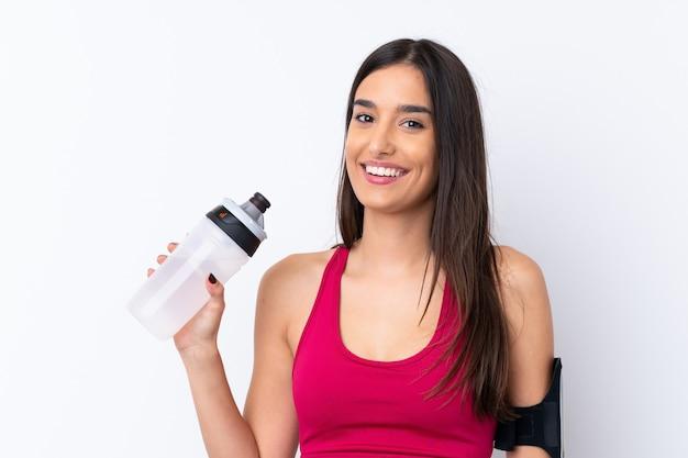 Jonge sport donkerbruine vrouw over geïsoleerde witte muur met de fles van het sportenwater