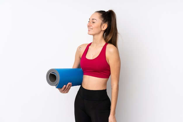 Jonge sport donkerbruine vrouw over geïsoleerde witte muur met een mat