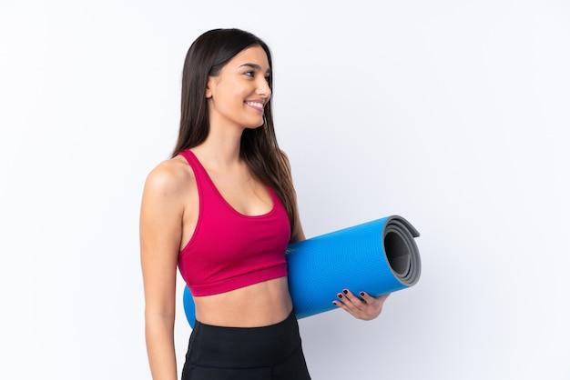Jonge sport donkerbruine vrouw over wit met een mat