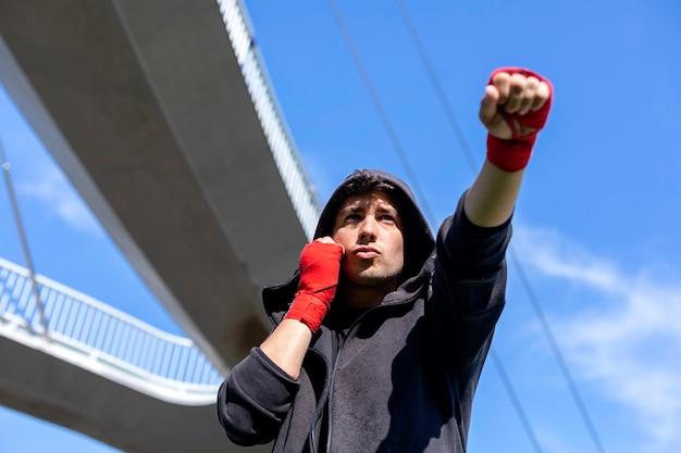 Jonge sport fitness man buiten in park maken boksoefeningen.