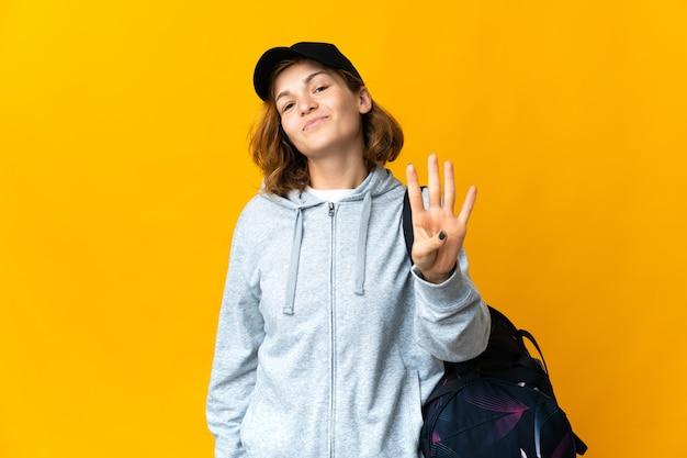 Jonge sport georgische vrouw met sporttas over geïsoleerde achtergrond gelukkig en vier tellen met vingers