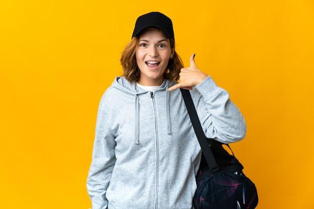 Jonge sport georgische vrouw met sporttas over geïsoleerde muur die telefoongebaar maakt. bel me terug teken