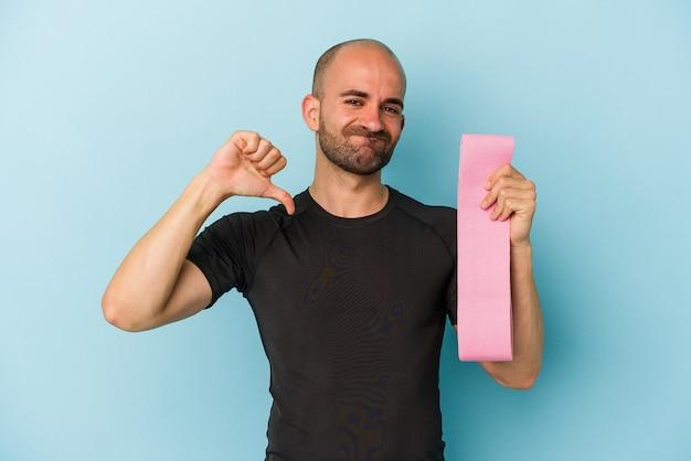 Jonge sport kale man met een elastische band geïsoleerd op blauwe achtergrond voelt zich trots en zelfverzekerd, voorbeeld om te volgen.
