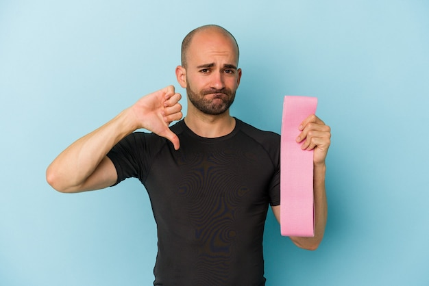 Jonge sport kale man met een elastische band geïsoleerd op een blauwe achtergrond met een afkeer gebaar, duim omlaag. onenigheid begrip.