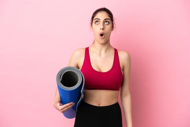 Jonge sport-kaukasische vrouw die naar yogalessen gaat terwijl ze een mat vasthoudt en omhoog kijkt en met een verbaasde uitdrukking