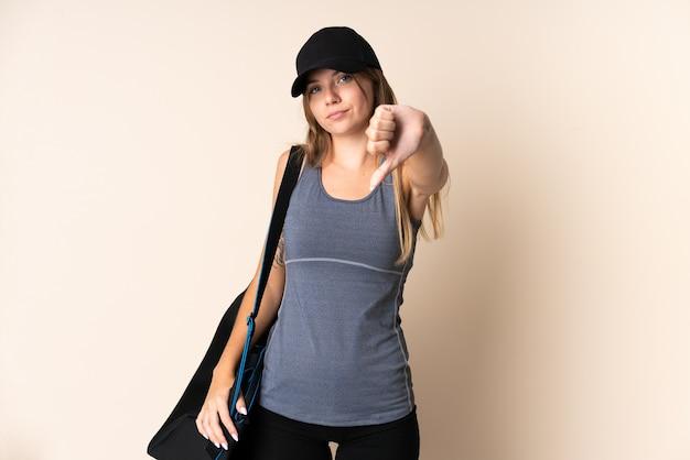 Jonge sport litouwse vrouw die een sporttas houdt die op beige achtergrond wordt geïsoleerd die duim met negatieve uitdrukking toont
