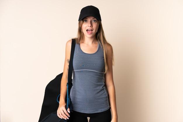 Jonge sport litouwse vrouw die een sporttas houdt die op beige met verrassingsgelaatsuitdrukking wordt geïsoleerd