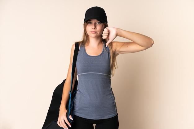 Jonge sport litouwse vrouw die een sporttas houdt die op beige wordt geïsoleerd die duim met negatieve uitdrukking toont