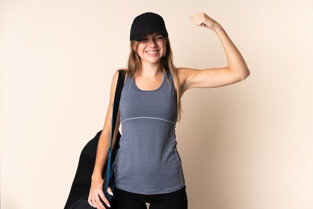 Jonge sport litouwse vrouw die een sporttas houdt die op beige wordt geïsoleerd die sterk gebaar doet