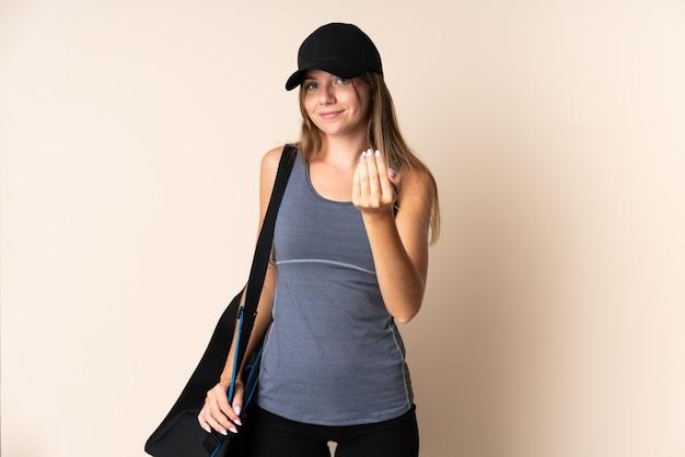 Jonge sport litouwse vrouw die een sporttas houdt die op beige wordt geïsoleerd die uitnodigt om met de hand te komen. blij dat je gekomen bent