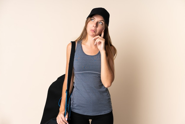 Jonge sport litouwse vrouw die een sporttas houdt die op beige wordt geïsoleerd en een idee denkt