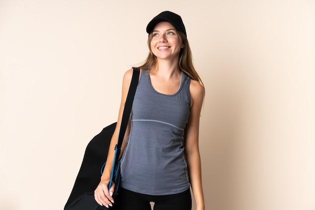 Jonge sport litouwse vrouw met een sporttas geïsoleerd op beige een idee denken tijdens het opzoeken