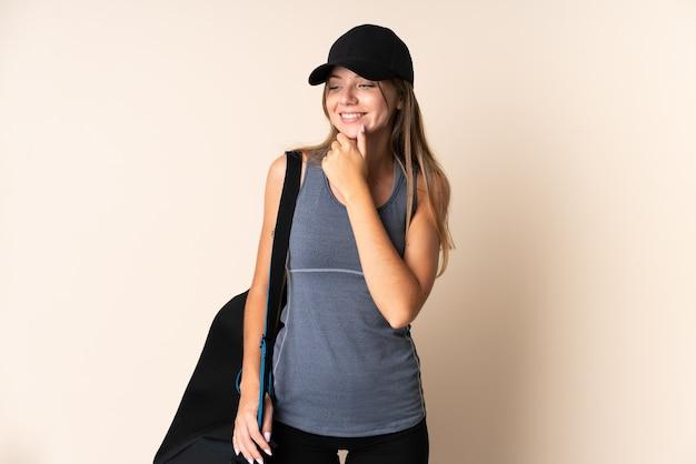 Jonge sport litouwse vrouw met een sporttas geïsoleerd op beige op zoek naar de zijkant en glimlachen