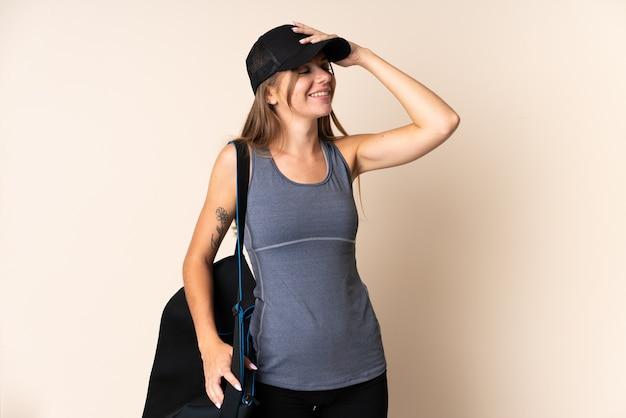 Jonge sport litouwse vrouw met een sporttas geïsoleerd op beige veel glimlachen