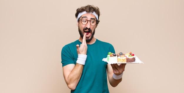 Jonge sport man met gebak tegen vlakke muur
