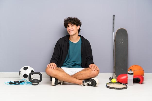 Jonge sport man zittend op de vloer rond veel sport elementen lachen en opzoeken