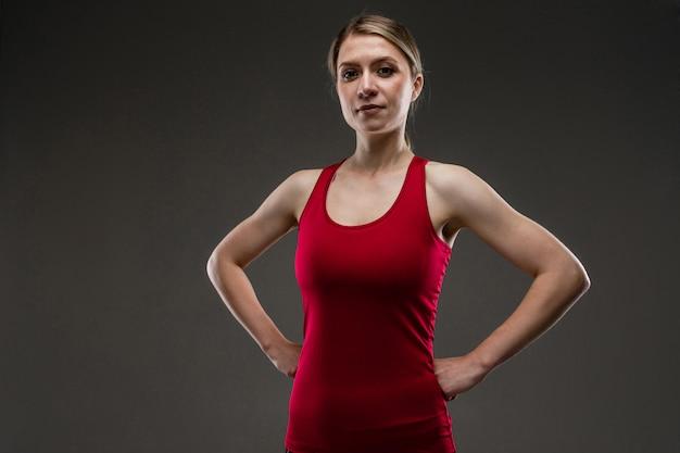 Jonge sport meisje met lang blond haar bedekt met staart, mooie uitstraling, sport lichaam, rood shirt, de moeite waard om handen op de riem te zetten