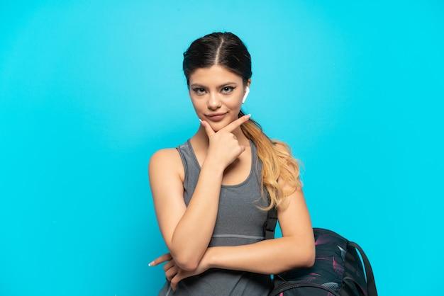 Jonge sport russisch meisje met sporttas geïsoleerd op blauwe achtergrond denken