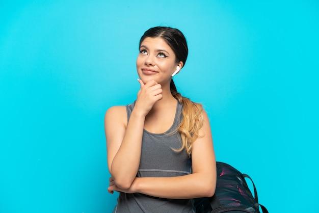 Jonge sport russisch meisje met sporttas geïsoleerd op blauwe achtergrond en opzoeken