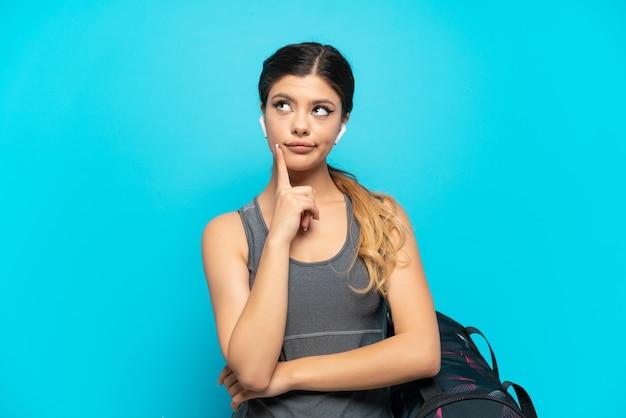 Jonge sport russisch meisje met sporttas geïsoleerd op blauwe achtergrond met twijfels en denken