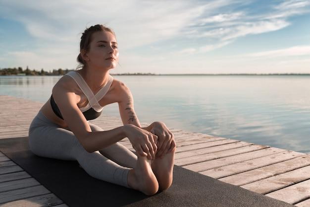 Jonge sport vrouw op het strand maken rekoefeningen.