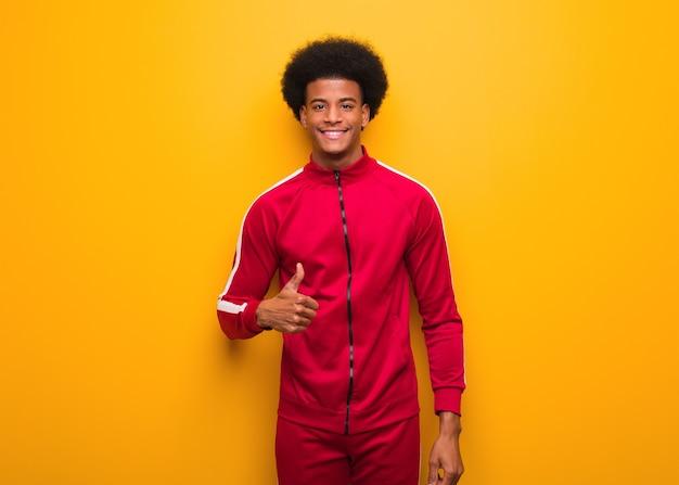 Jonge sport zwarte man op een oranje muur glimlachend en duim opheffen