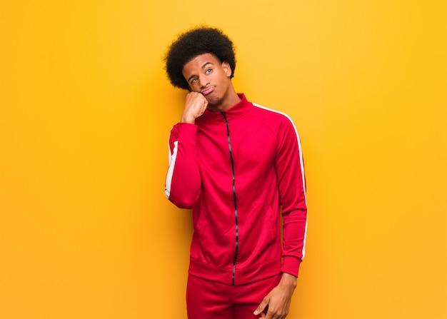 Jonge sport zwarte man over een oranje muur denken aan iets, op zoek naar de kant