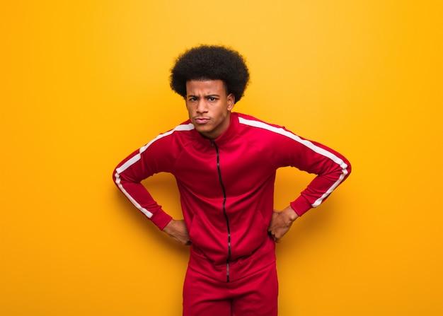 Jonge sport zwarte man over een oranje muur die iemand erg boos berispt