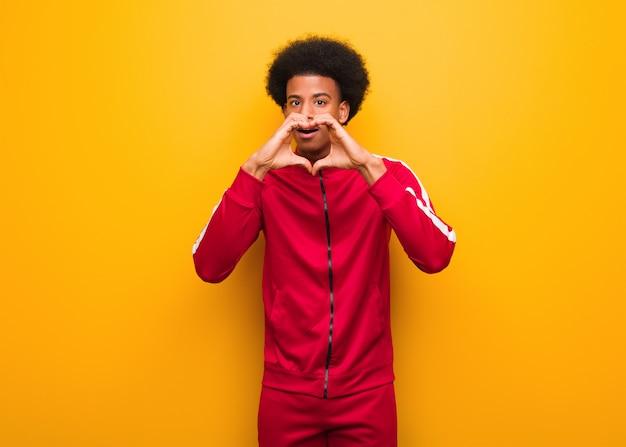Jonge sport zwarte man over een oranje muur doet een hartvorm met handen