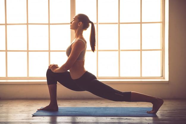 Jonge sportdame die yoga in fitness zaal doet