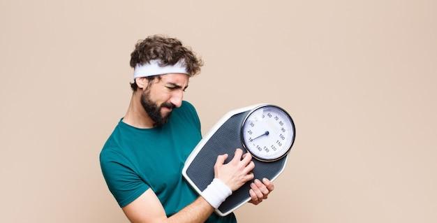 Jonge sportenmens die een gewichtsschaal houden tegen vlakke muur
