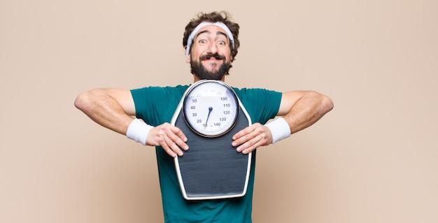 Jonge sportenmens die een gewichtsschaal op muur houden