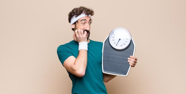 Jonge sportenmens die een gewichtsschaal op vlakke muur houdt