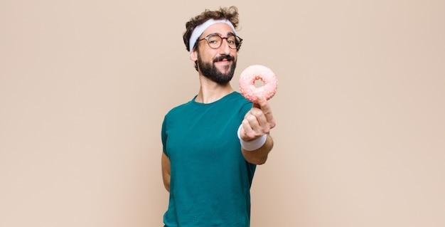 Jonge sportenmens die een snack heeft die een roze suikerdoughnut houdt
