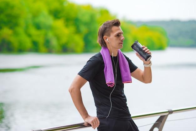 Jonge sportenmens met handdoek en fles water na in openlucht het aanstoten