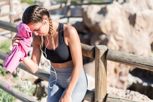 Jonge sportenvrouw die en haar zweet rusten afvegen met een handdoek.