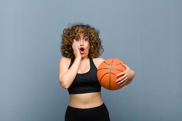 Jonge sportenvrouw die fitness kleren met een mandbal draagt