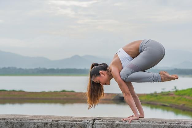 Jonge sportenvrouw die yoga op het meer met bergachtergrond doen.
