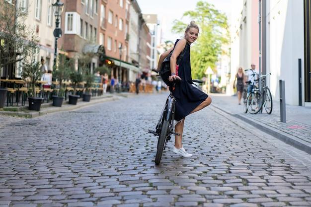 Jonge sportenvrouw op een fiets in een europese stad. sporten in stedelijke omgevingen.