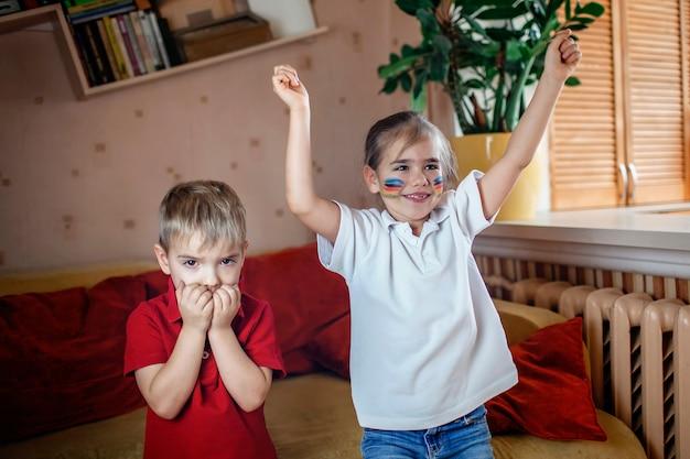 Jonge sportfan die sport op spelen letten en thuis voor haar team op tv toejuichen