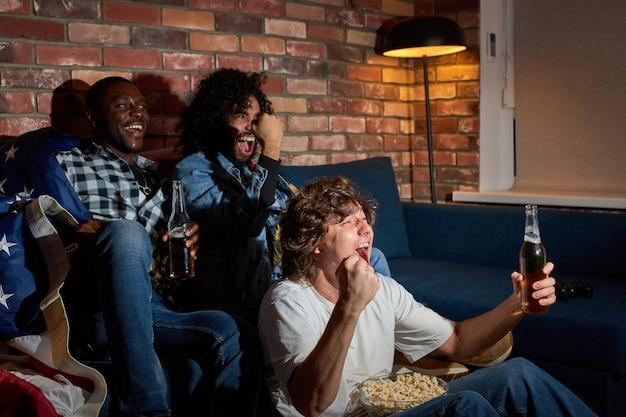 Jonge sportfans vieren de overwinning thuis. gepassioneerde supporters schreeuwen naar de wedstrijd op tv, juichen samen, schreeuwen emotioneel